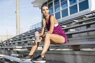 Thoughtful sporty woman sitting on bleachers at stadium - CAVF40213