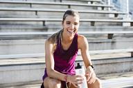 Cheerful female athlete sitting on bleachers - CAVF40216