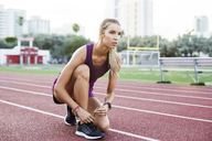 Confident female athlete tying shoelace on race tracks - CAVF40219