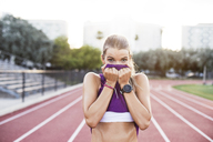 Portrait of sporty woman wiping sweat on face with tank top at field - CAVF40222