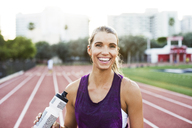 Portrait of happy woman holding water bottle on race tracks - CAVF40225