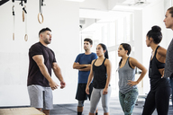 Athletes listening to instructor explaining in crossfit gym - CAVF40237