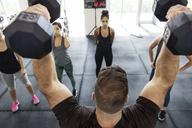Instructor lifting dumbbells while explaining athletes in crossfit gym - CAVF40240