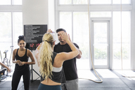 Man giving high-five to female athlete at crossfit gym - CAVF40246