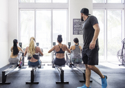 Instructor looking at athletes exercising in crossfit gym - CAVF40249