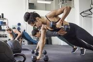 Female athletes doing push-ups using dumbbells in crossfit gym - CAVF40255