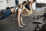Athletes doing burpee exercise in crossfit gym - CAVF40258