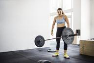 Female athlete throwing barbell in crossfit gym - CAVF40270