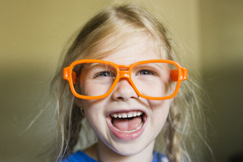 Happy girl with sunglasses frame at home - CAVF40306