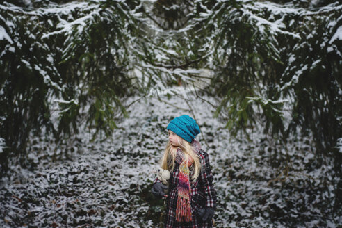 Girl with stuffed toy standing at backyard during winter - CAVF40327