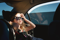 Girl in sunglasses sitting in car - CAVF40330