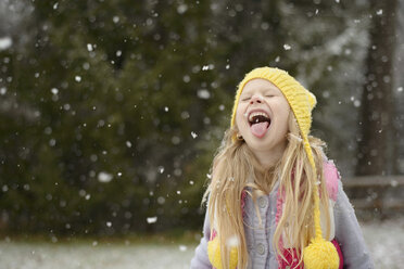 Playful girl sticking out tongue during snowfall - CAVF40336