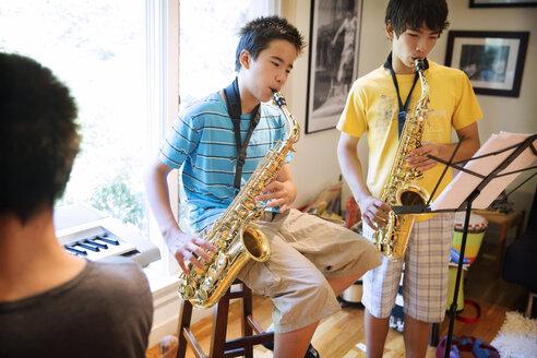 Siblings practicing saxophones at home - CAVF40402