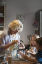Woman adding sugars in dough while making cookies with children in kitchen - CAVF40477