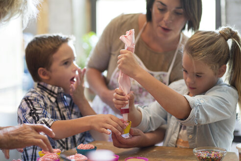 Family making cupcakes in kitchen - CAVF40492