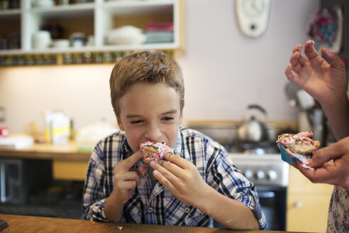 Boy eating cupcake while standing in kitchen - CAVF40495