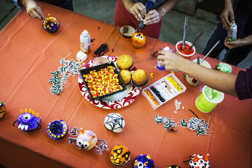 Mother and children decorating muffins at table during Halloween party - CAVF40540