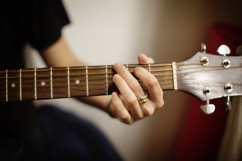 Cropped image of woman playing guitar at home - CAVF40546
