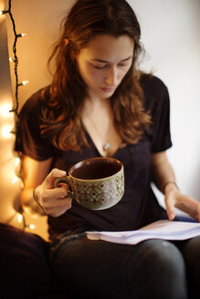 Serious woman holding coffee cup while reading book at home - CAVF40549