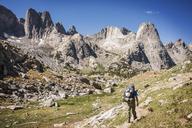 Rear view of hiker walking on field by rock formations - CAVF40573