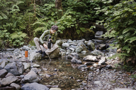 Hiker filling water bottle while sitting on rock at lakeshore in forest - CAVF40675