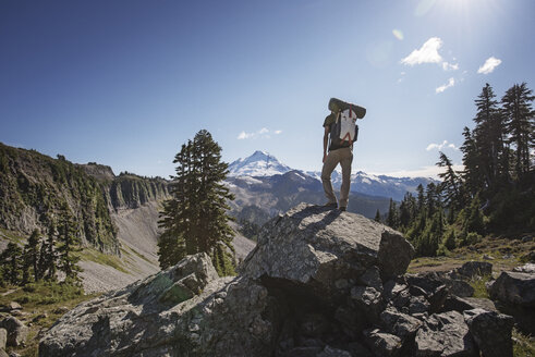 Rear view of hiker standing on rock amidst mountains against sky - CAVF40678