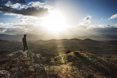 Hiker standing on rock by mountains against sky on sunny day - CAVF40696