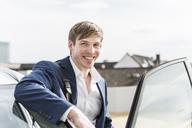 Portrait of smiling businessman at car - UUF13415