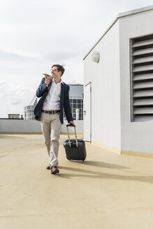 Smiling businessman with rolling suitcase using smartphone at parking garage - UUF13418