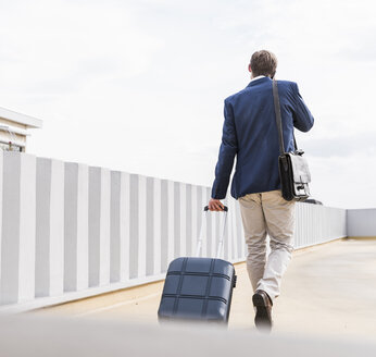 Rear view of businessman with rolling suitcase using smartphone at parking garage - UUF13421
