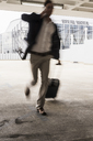 Businessman with rolling suitcase in a hurry at parking garage - UUF13424