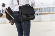 Businessman with and skateboard walking at parking garage - UUF13430