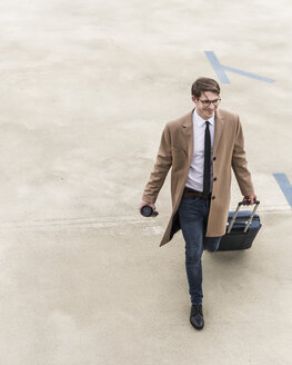 Smiling businessman with rolling suitcase walking at parking garage - UUF13436