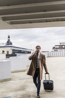 Businessman with rolling suitcase and smartphone walking at parking garage - UUF13442