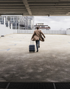 Businessman with rolling suitcase in a hurry at parking garage - UUF13445