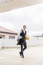 Smiling businessman with basketball walking at parking garage - UUF13448