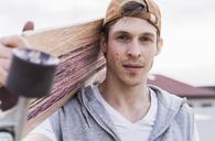 Portrait of man carrying skateboard - UUF13463