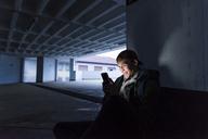 Smiling man looking at shining smartphone in parking garage - UUF13469