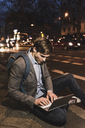 Businessman using laptop on urban street at night - UUF13472