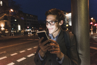 Smiling businessman using cell phone on urban street at night - UUF13475