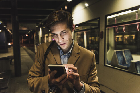 Businessman using cell phone at tram station at night - UUF13478