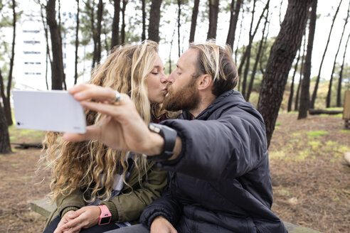Romantic couple kissing while taking selfie through smart phone in forest - CAVF40822