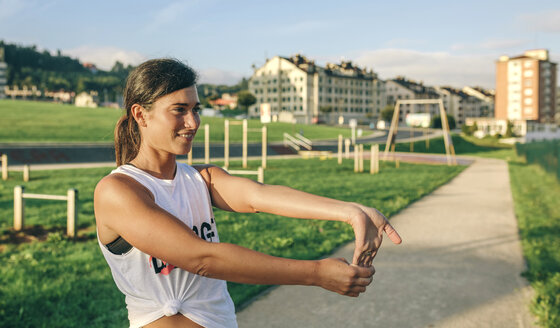 Woman looking away while stretching wrist at park - CAVF40843