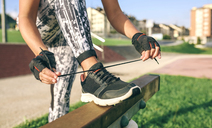 Low section of woman tying shoelaces at park - CAVF40849