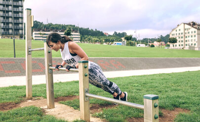 Side view of woman doing push-ups on gymnastics bar at park - CAVF40861