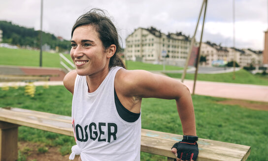 Happy woman exercising at park - CAVF40867