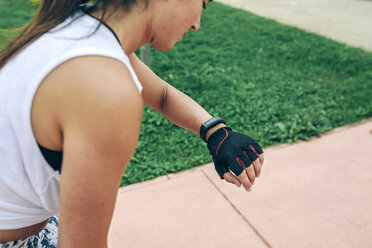 Woman looking at smart watch while exercising at park - CAVF40870