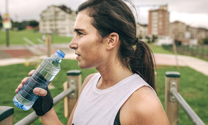 Woman looking away while holding water bottle at park - CAVF40876
