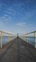 Rear view of boy walking on pier over river against cloudy sky - CAVF40909