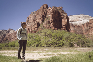 Woman standing by mountain at Zion National Park - CAVF40921